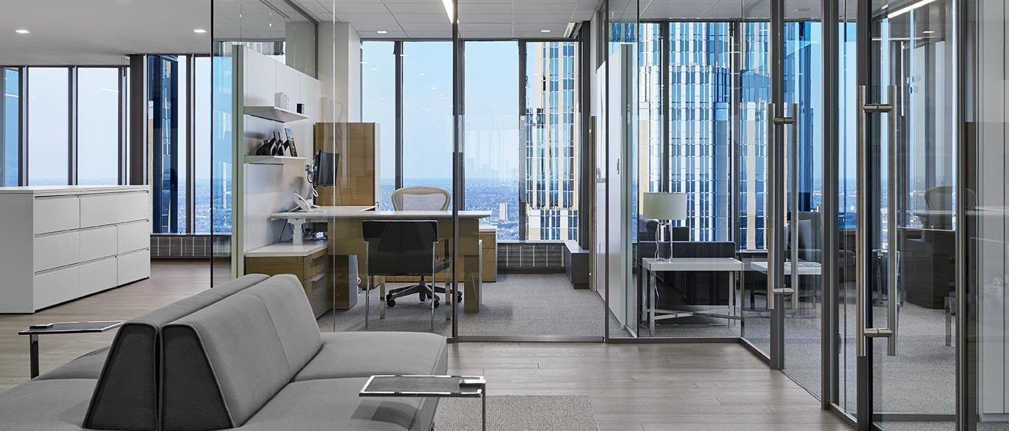 Office space with glass windows, an office chair, and office desk