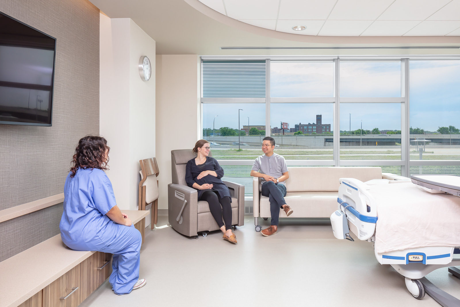 Nurse talking to pregnant woman and a man in a hospital room