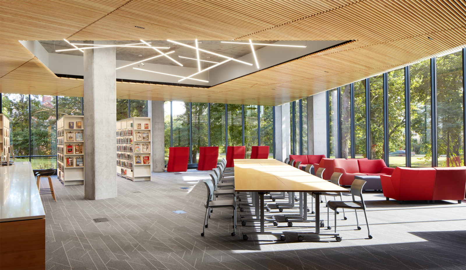 A library space with a long table and red chairs