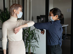 Two women bumping elbows with masks over their nose and mouth