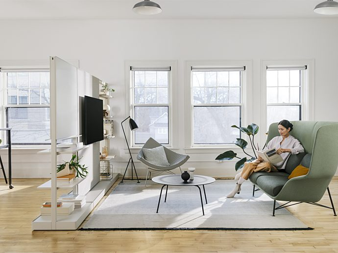 Woman sitting on green chair in living room