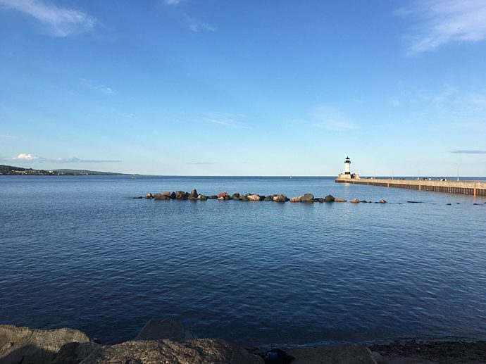 Lake with big rocks in the middle and a boardwalk with a light house