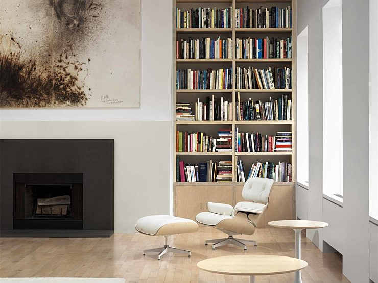 Eames Lounge chair in white leather in front of a fireplace and floor to ceiling bookshelf in a modern living room