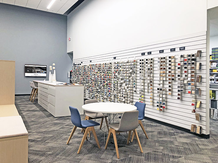 Design resource library featuring a collaborative high-top, a small group table, and a wall of fabric swatch samples